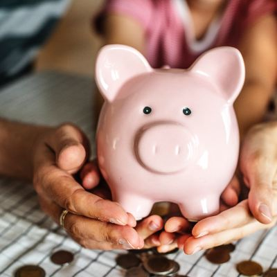 Hands holding a piggy bank - Giant List Of Family Activities For A No-Spend Weekend