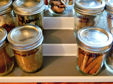 In a cool, empty upper cabinet, my excess spices are stored in jars.