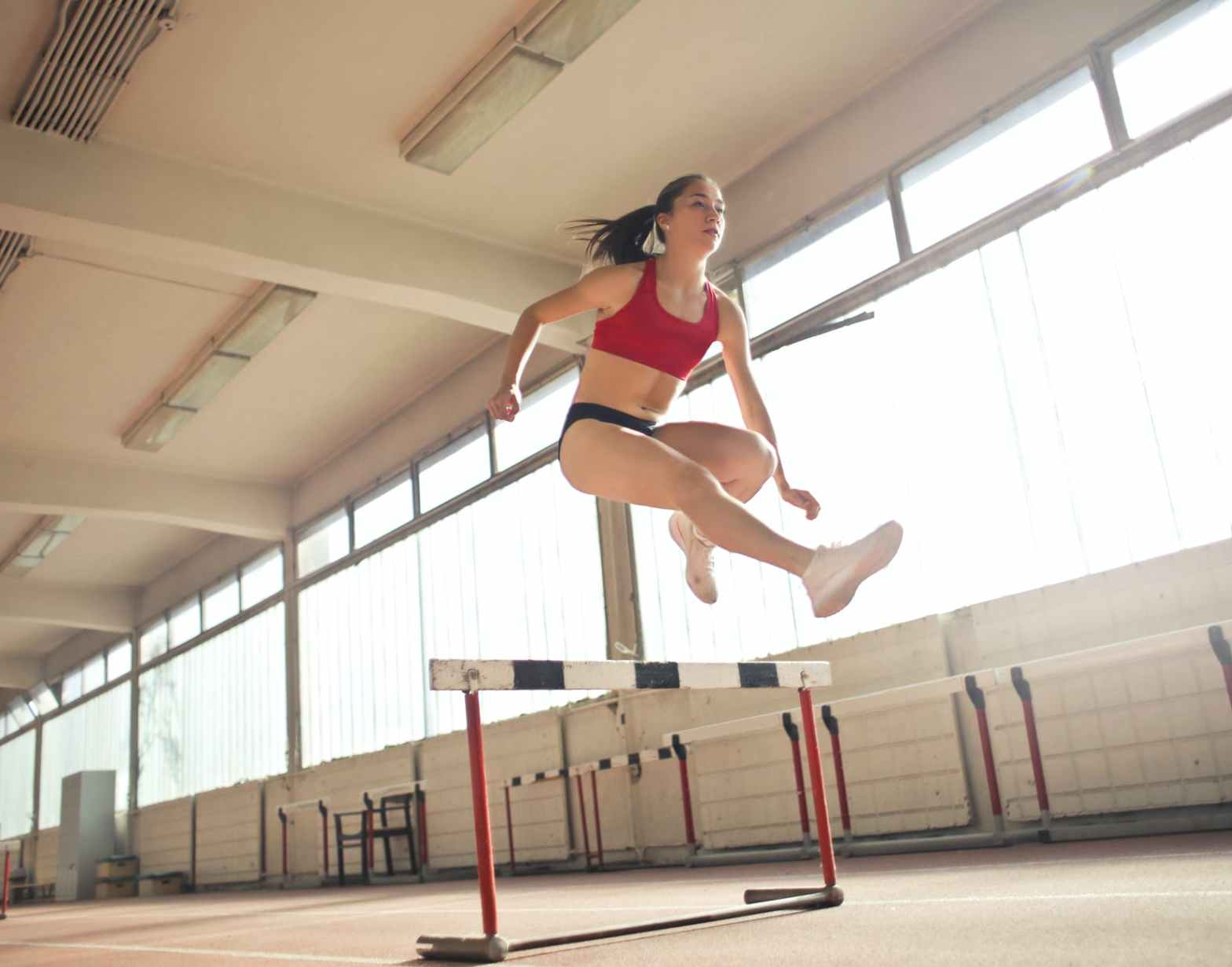 photo of a woman jumped on obstacle