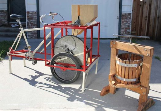 Our pedal-powered apple crusher on the left shreds up the fruit which is then pressed in the oak press on the right.