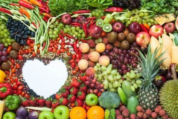 A white heart shape embedded in a display of colorful fruits and vegetables.