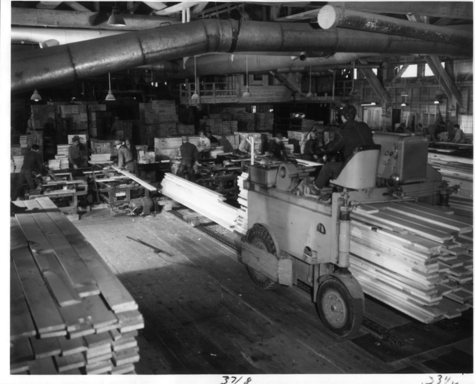 Groups of Workers Inside Factory Lifting Wood and Stacking it Neatly in Piles