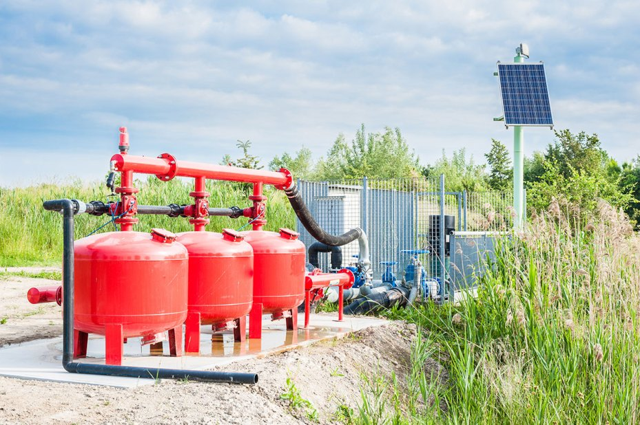 Solar Pumps Red With Blue Sky in the Background and Grass Behind