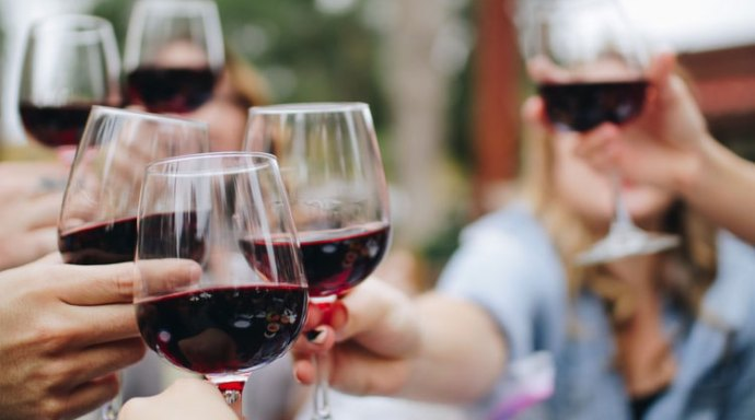 Hands toasting glasses of red wine