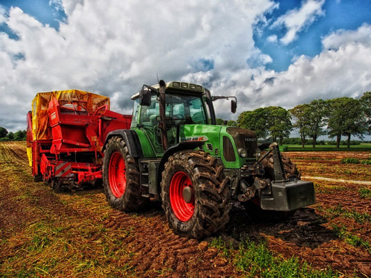 A green tractor with a grain mixer in a field