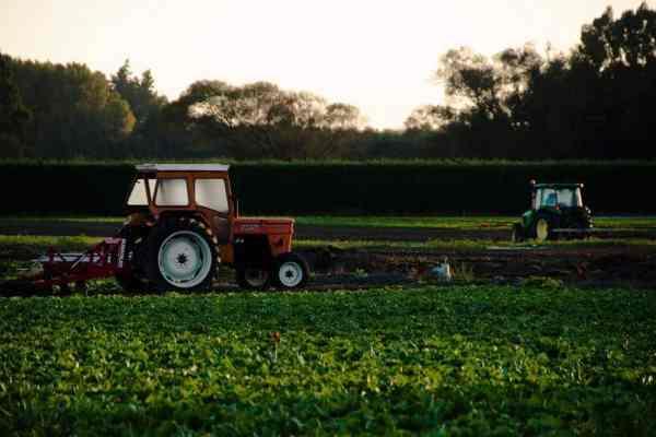 Tractors plowing a field in low light