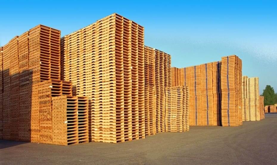 Large stacks of wooden pallets in an asphalted lot in the daytime.