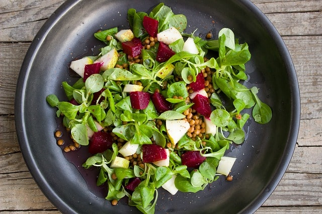 A plate of beetroot and pear salad with small leafy greens