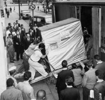 Several workers loading an early hard drive that's taller than they are into a truck