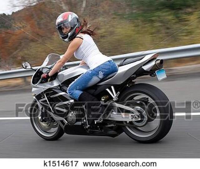 A Pretty Blonde Girl In Action Driving A Motorcycle At Highway Speeds