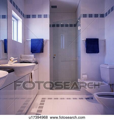 bleu serviettes sur non plus cote de porte verre a douche dans moderne blanc salle bains a bleu carreau detail banque de photo