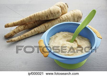 Bowl of parsnip puree and parsnips on grey wooden table Stock Image   ipf000021   Fotosearch