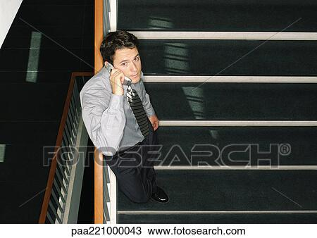 Man Standing On Stairs Using Cell Phone High Angle View