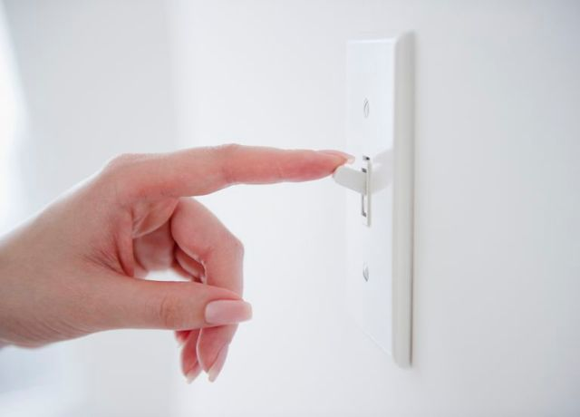 woman flipping light switch