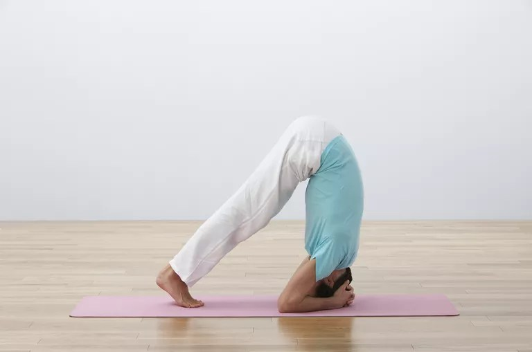 Man bent over on exercise mat, performing headstand, side view