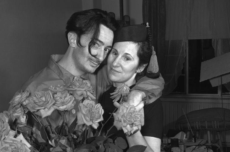 Salvador Dalí ve eşi bir buket gülünün arkasında kucaklıyor