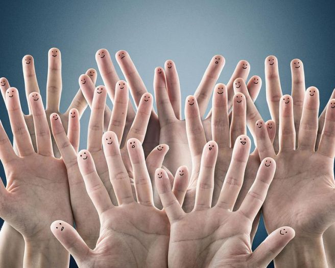 a group of hands with happy faces painted on each finger.