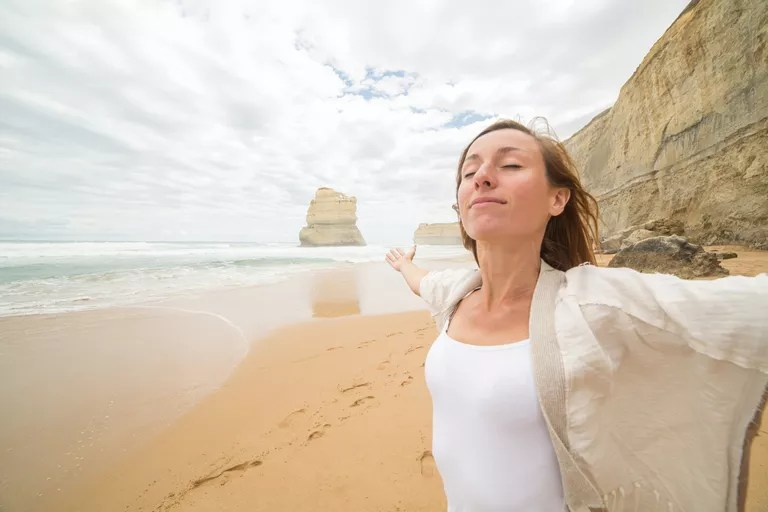 Young woman arms outstretched on Gibsons steps beach, Australia