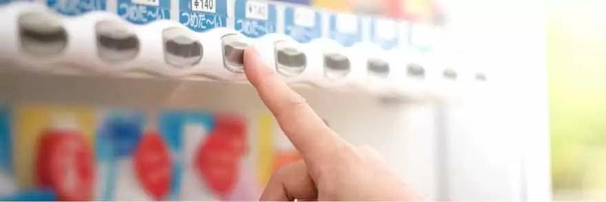 自動販売機のボタンを押す