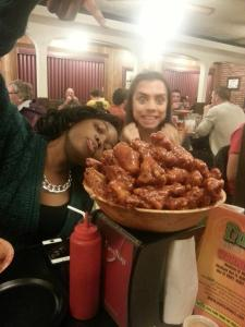 This is an presh photo of a coworker and I eating chicken wings at a conference.