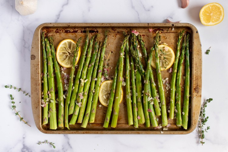 Image of asparagus on a baking sheet sprinkled with thyme, garlic, and shallots.