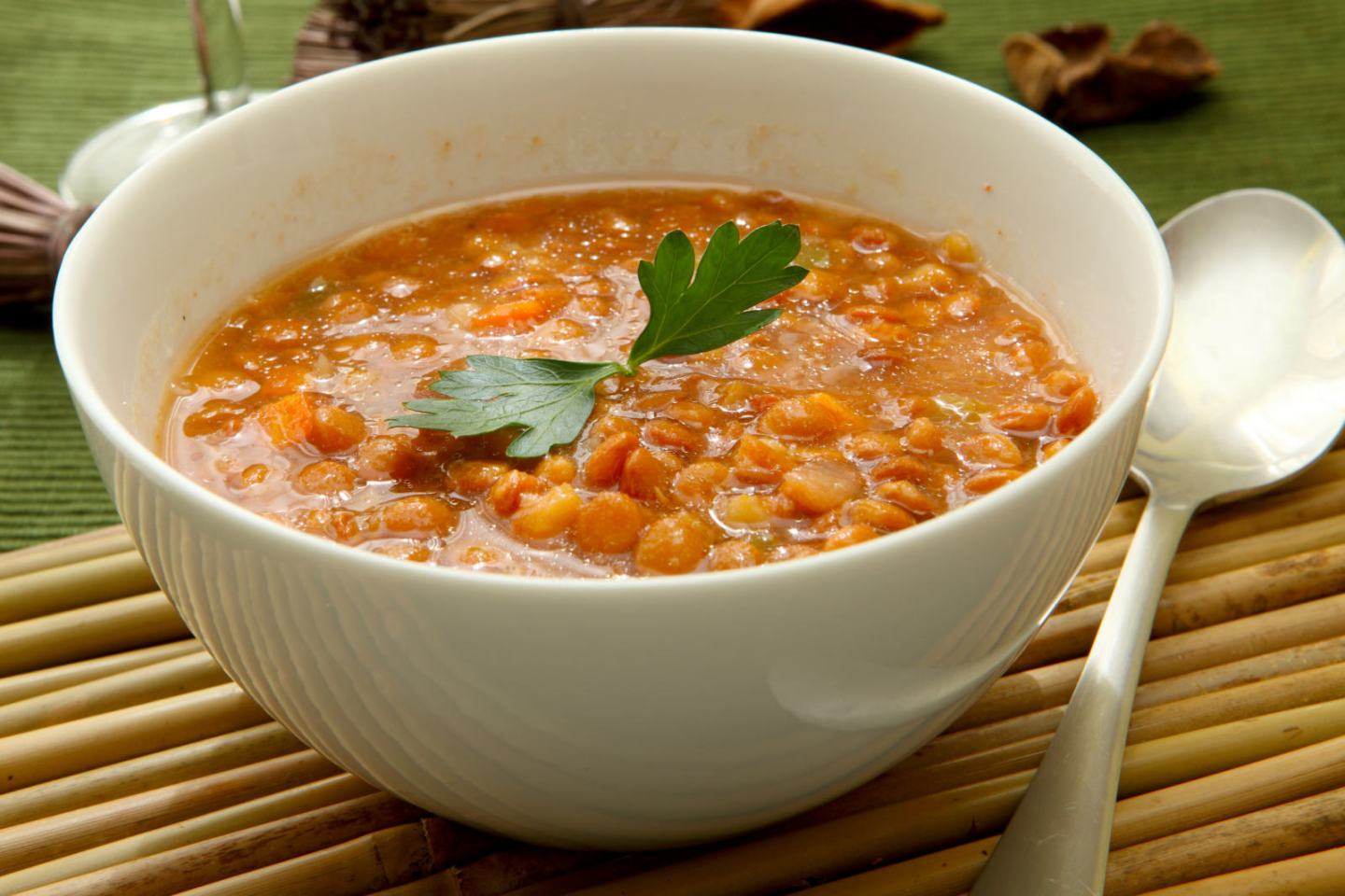 a white bowl of lentil soup with parsley