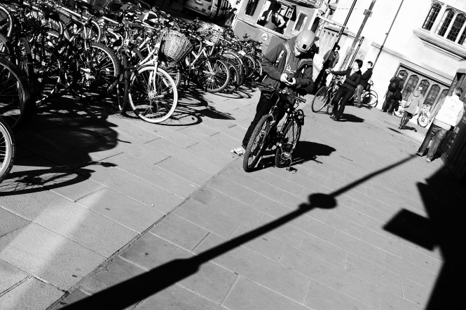 """The bright sun meant that to me, the 'angles' would need to come from shadows. This guy caught my eye because he was using his phone before getting on his bike. I wondered who he was contacting, or whether he was just checking a map. About 20 mins later we saw a cyclist nearly get taken out by a car so I wonder now if he was sending a ritual """"goodbye, just in case"""" message. X-T1; XF18-55 @ 35; 1/640 sec; f/5.6; ISO 200"""