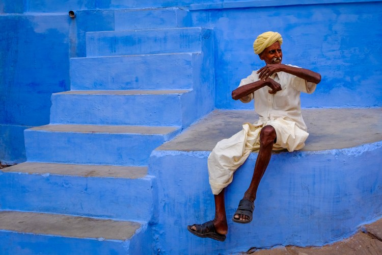 A man sits on blue steps outside his house in Jodhpur Old City, Rajasthan, India. Jodhpur is also known as the blue city because of the large number of houses and walls painted blue which, according to the locals, repels termites which are a problem in the area.