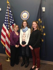 Three women standing in front of an American flag and the Indiana state flag in the office of a U.S. Senator.
