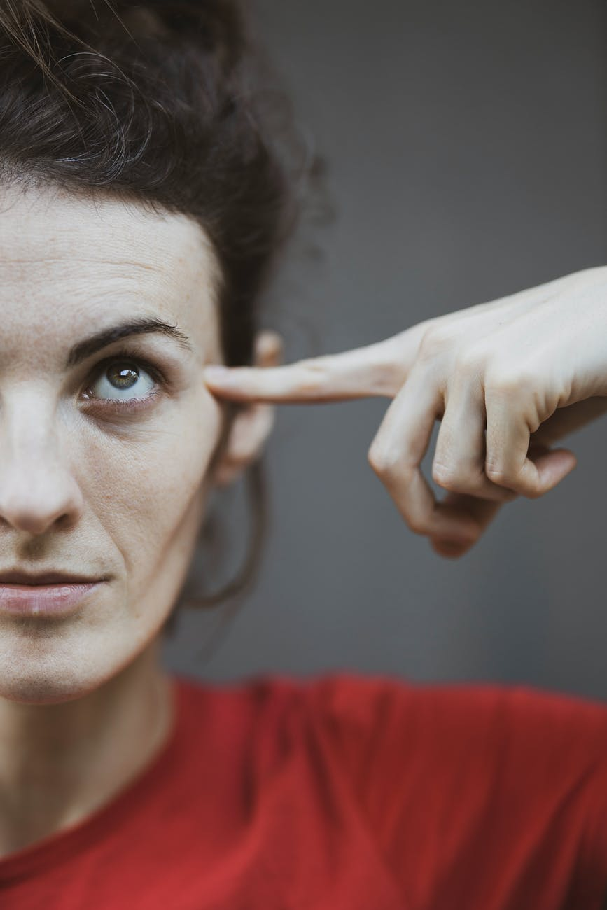 selective focus portrait photo of woman in red t shirt pointing to her head
