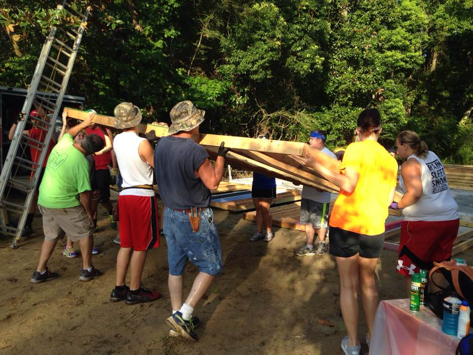 Volunteers raise the first wall of the Bennett home on Monday.