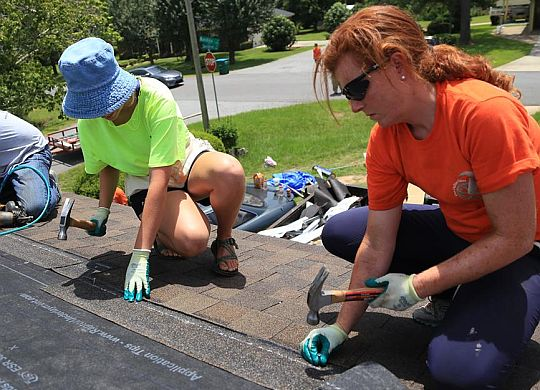 Bicycle Adventurers repair roof in Albany, Ga., on last build day of cross-country ride