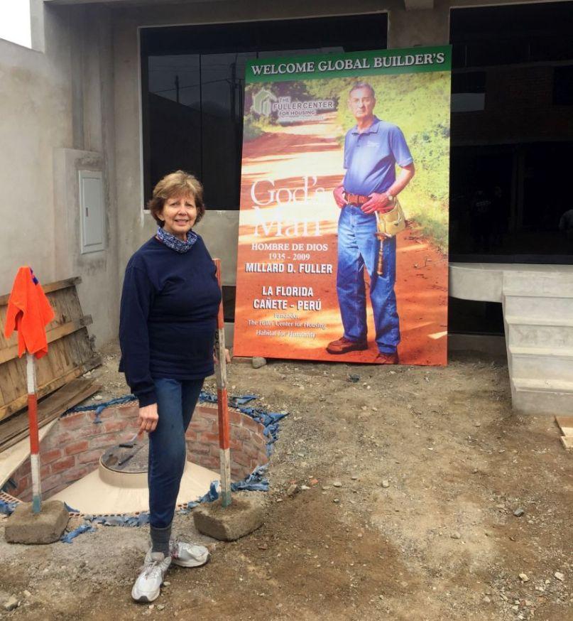 Linda Fuller beside a Millard Fuller poster in La Florida.