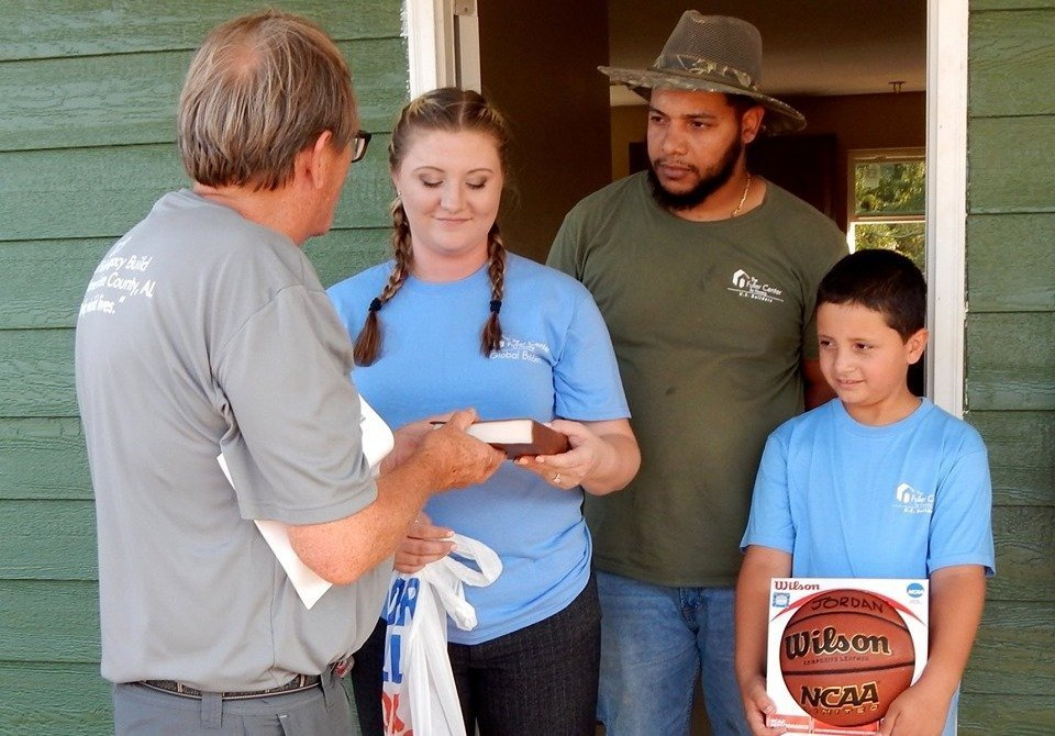 President David Snell presents a Bible to the Melton family, who lost a son in the March 3 Alabama tornado.
