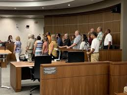 group of men and women turned to right with right hand raised - in a brown jury box facing a white wall