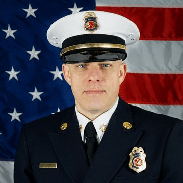 White male, wearing white fire chief hat, blue uniform with white shirt, American Flag behind him