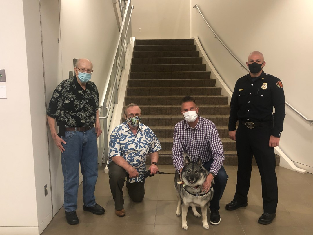 four white males, two kneeling, norwegian elkhound service dog in center stair case behind group