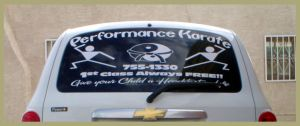 Karate decals advertising business on back window glass