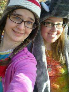 Image description: Me, a pale brunette wearing a purple sweatshirt and Anna, a pale blonde wearing a tie-dye shirt, both smiling at the camera.