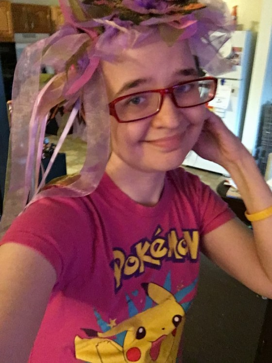 Image is of a brunette female with blue eyes and red glasses. She is wearing a flower crown and a pink pokemon t shirt. I don't know why I'm wearing the crown. It seemed fun.