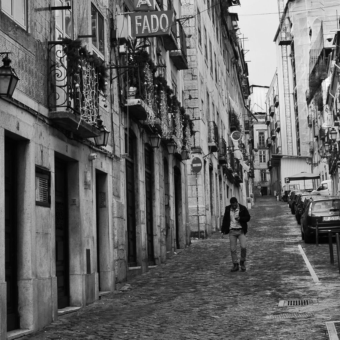 Man strolls in the Bairo Alto of Lisbon, the fado singing district packed with great restaurants featuring traditional dishes.