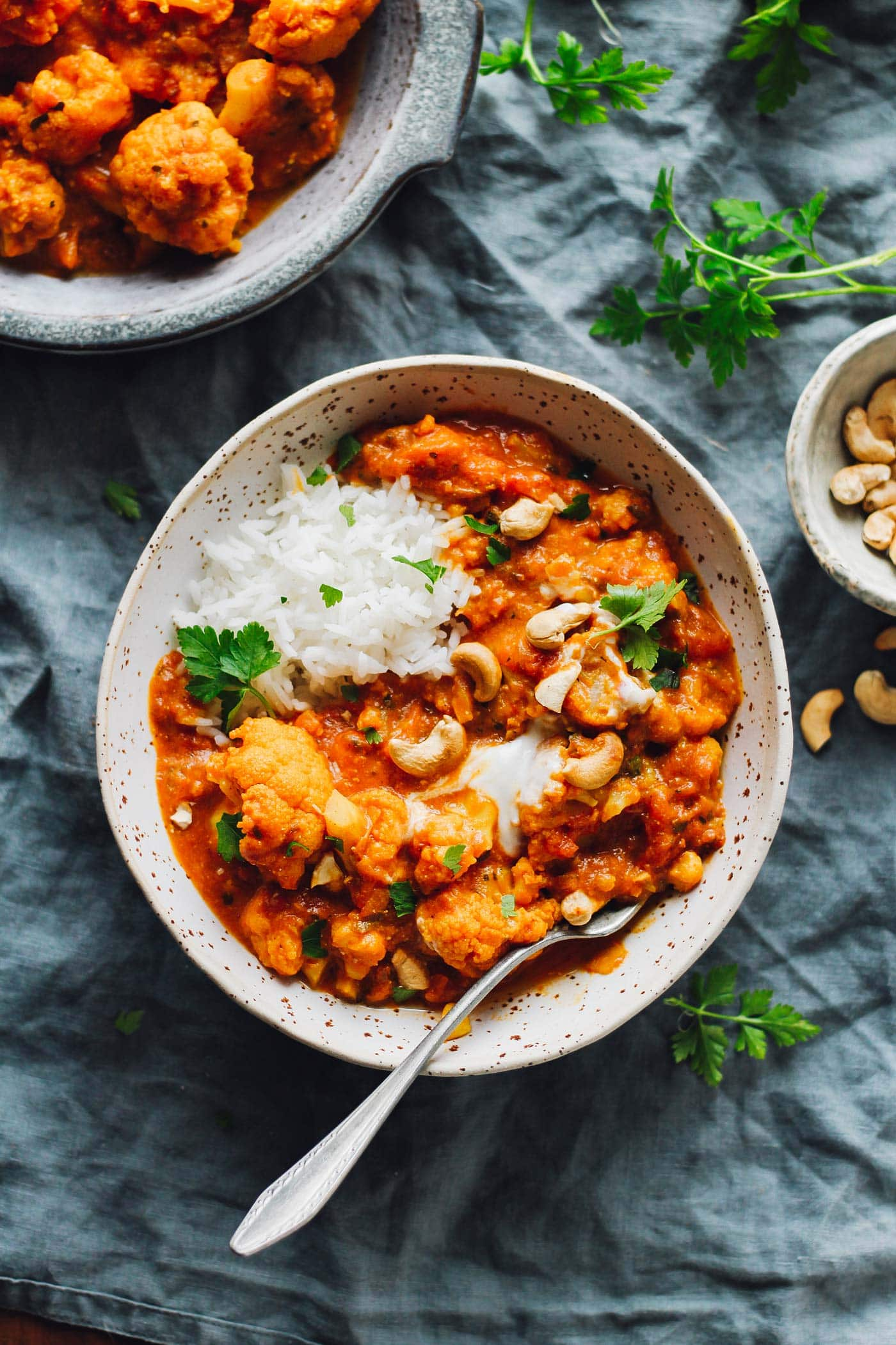 Instant Pot Cauliflower Tikka Masala in a bowl with roasted cashews, cilantro, and rice.