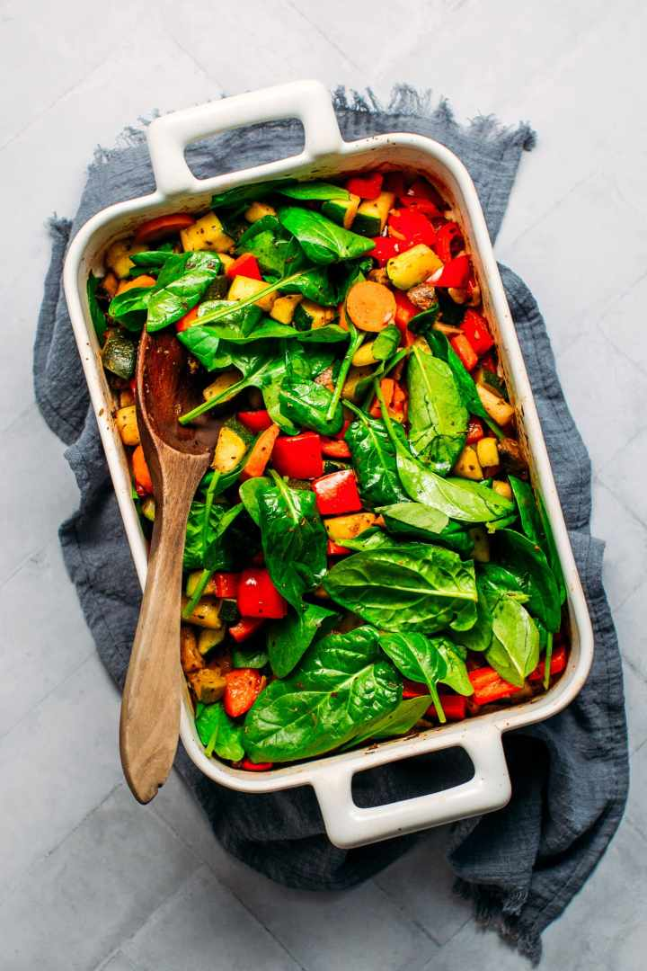 Roasted veggies in baking dish with spinach.