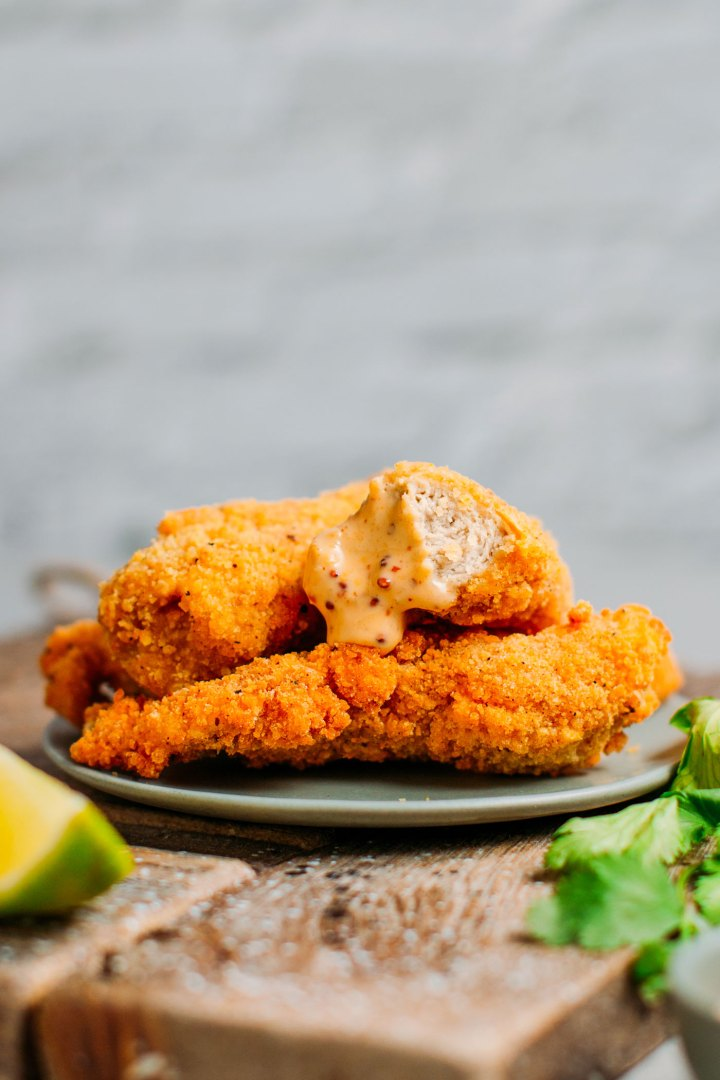 Vegan chicken nuggets dipped in mustard dipping sauce.