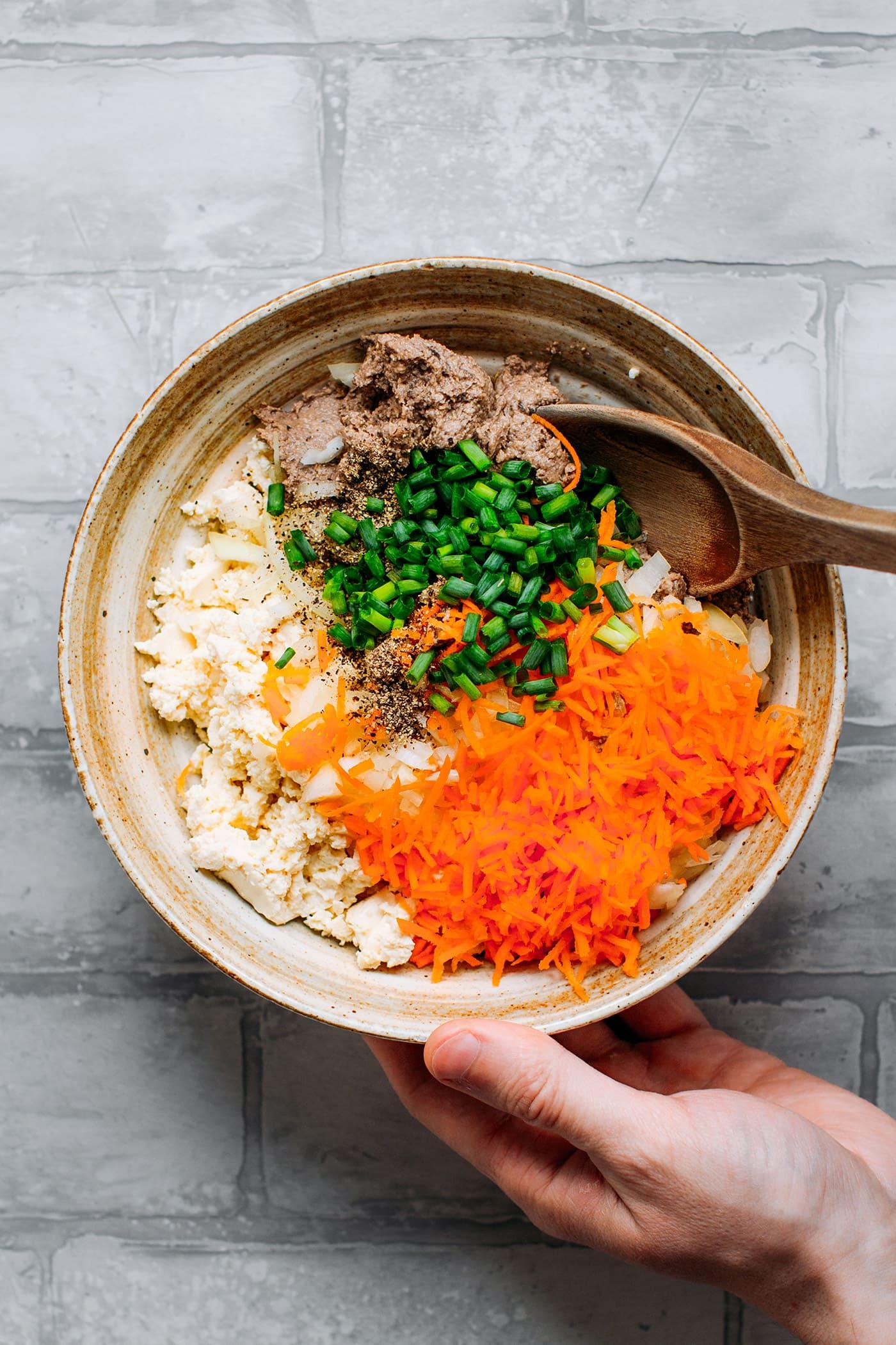 Tofu, green onions, carrots, vegan paté, and garlic in a bowl.