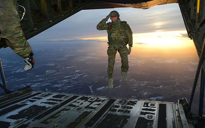 10. Американский военный отдает честь во время прыжка с самолета С-130 Hercules.