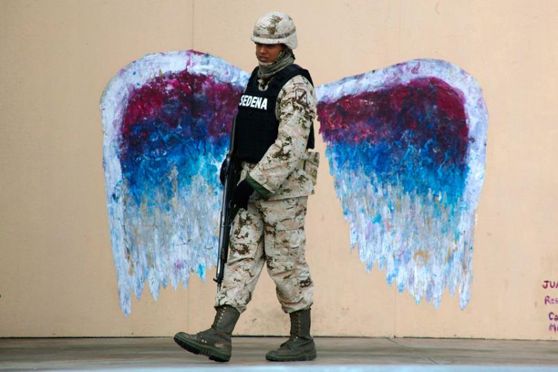 22. Удачный кадр, запечатлевший солдата на фоне граффити с изображением крыльев ангела.