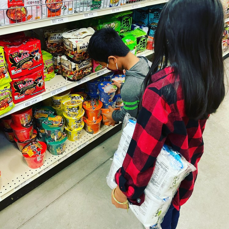 Image of Bowen, a small Asian boy with Dwarfism, bent down choosing two bowls of noodles from the bottom shelf of a grocery aisle. His sister, Tess, a small Asian girl with long black hair is standing in the background. She is wearing a plaid flannel shirt and holding a multi-pack of dried seaweed under her arm.