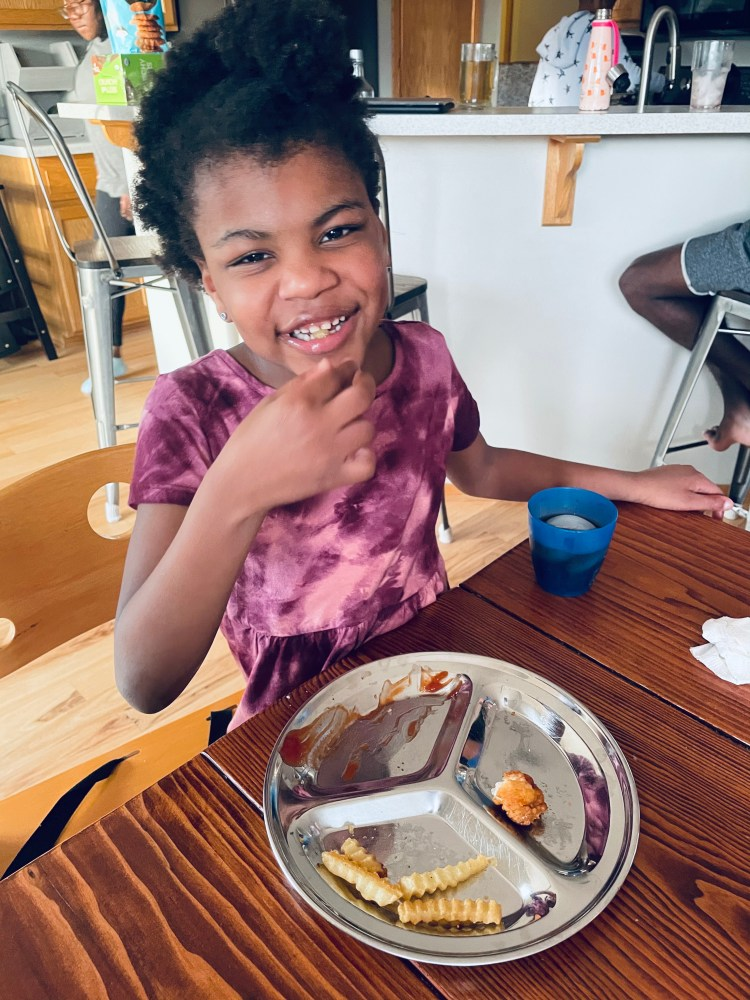 Isabel, a small Black girl in a dark purple dress, eating chicken nuggets and French fries off of a silver plate while smiling for the camera.