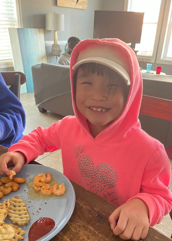 Gigi, a small Asian girl, wearing a khaki cap with a pink hoodie pulled up over it, smiles for the camera. She smiling widely over a plate of shrimp and waffle fries with ketchup.